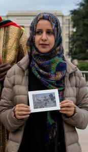 Radhya Almutawakel pitää käsissään kuvaa kotimaansa pääkaupungin kauneudesta ja tuhosta. Kuva: Control Arms